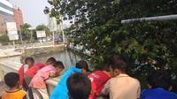 Anak-anak berkerumun di sekitar lokasi sarang buaya (Liputan6.com/Delvira)