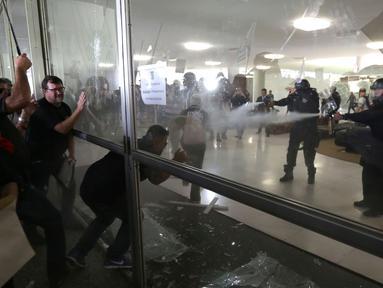 Sejumlah polisi Brasil memecahkan kaca saat mencoba masuk ke Gedung Kongres Nasional Brasil selama unjuk rasa di Brasilia (18/4). Aksi ini sebagai bentuk protes terhadap RUU perubahan aturan pensiun. (AP Photo / Eraldo Peres)
