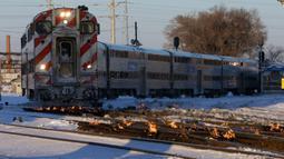 Sebuah kereta komuter melaju menuju pusat kota Chicago ketika api menyala di sepanjang rel di dekat stasiun Metra Western Avenue, 29 Januari 2019. Metra memakai sistem pemanas berbahan bakar gas untuk menghangatkan lintasan yang dingin. (AP/Kiichiro Sato)