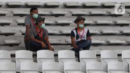 Pewarta mengenakan masker saat meliput laga kualifikasi Grup H Piala AFC 2020 antara PSM Makassar melawan Kaya FC-Iloilo, Jakarta, Selasa (10/3/2020). Pertandingan dilaksanakan tanpa dihadiri penonton sebagai antisipasi penyebaran virus Corona COVID 19. (Liputan6.com/Helmi Fithriansyah)