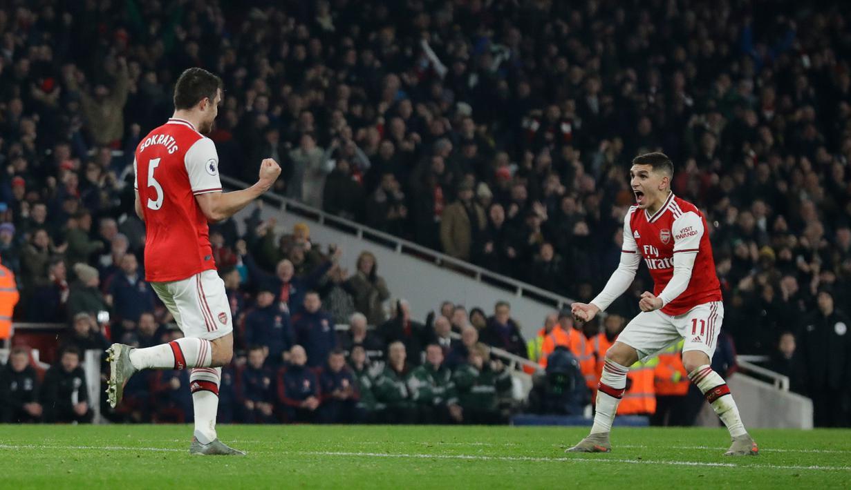 Pemain Arsenal Sokratis Papastathopoulos (kiri) merayakan dengan rekan setimnya Lucas Torreira usai mencetak gol ke gawang Manchester United pada pertandingan lanjutan Liga Inggris di Emirates Stadium, London, Rabu (1/1/2020). Arsenal menang 2-0. (AP Photo/Matt Dunham)