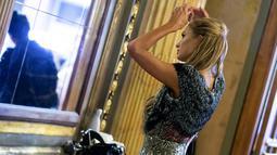 """Sosialita AS Paris Hilton merapihkan rambutnya sebelum ia berjalan di karpet merah menghadiri pemutaran perdana """"The Death and Life of John F. Donovan"""" selama Festival Film Internasional Toronto di Toronto, Ontario, Kanada (10/9). (AFP Photo/Geoff Robins)"""