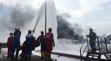 Tim HSSE & Fire Fighter Pertamina berupaya memadamkan api pada kebakaran tangki minyak Pertamina RU VI Balongan, Indramayu, Rabu (31/3/2021). Memasuki hari ketiga pascakebakaran, tim Emergency Pertamina berhasil memadamkan tiga tangki dari total empat tangki yang terbakar. (Dok. Humas Pertamina)
