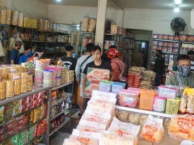 Pekerja membawa kardus berisi kue kering di salah satu toko penjualan kue kering di kawasan Ciracas, Jakarta, Selasa (19/5/2020). Adanya pandemi covid-19 diakui para pedagang menyebabkan penjualan kue kering menjelang lebaran turun hingga 50 persen. (Liputan6.com/Immanuel Antonius)