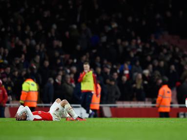 Gelandang Arsenal, Theo Walcott (kiri) dan Nacho Monreal terlihat sedih usai pertandingan melawan Swansea City pada lanjutan liga Inggris di Stadion Emirates (2/3). Swansea menang atas Arsenal dengan skor 2-1. (Reuters/Dylan Martinez)