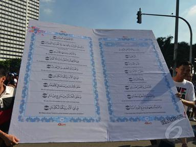 Aktivis yang tergabung dalam Quran Generation membawa Alquran raksasa di Bundaran HI, Jakarta, Minggu (21/12/2014). (Liputan6.com/Herman Zakharia)
