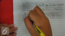 Seorang siswa menulis surat untuk Presiden RI Joko Widodo di SDN Sukasari 4 Kota Tangerang, Selasa, (29/16). Isi Surat Siswa-siswi tersebut meminta Presiden Jokowi bisa hadir ke sekolahan kami di SDN Sukasari 4 Kota Tangerang. (Liputan6.com/Faisal R Syam)