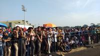 Warga berdesakan di Taxy Way Echo Halim Perdankusuma untuk menyaksikan perayaan HUT TNI. (Liputan6.com/Ady Anugrahadi)