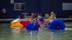 Sejumlah orang menaiki perahu kayuh di danau buatan Bassin de la Villette dalam acara Paris Plages, Paris, Prancis, 18 Juli 2020. Acara Paris Plages digelar dari 18 Juli hingga 30 Agustus, menawarkan beragam kegiatan di tepi Sungai Seine dan Bassin de la Villette. (Xinhua/Aurelien Morissard)