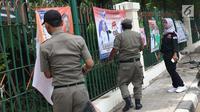 Petugas Satpol PP bersama Panwaslu kecamatan Ciracas menurunkan APK yang terpasang di pagar pembatas antara jalan dengan taman di pinggir kali di sekitar Jalan Raya Bogor, Jakarta, Rabu (23/1). (Liputan6.com/Helmi Fithriansyah)