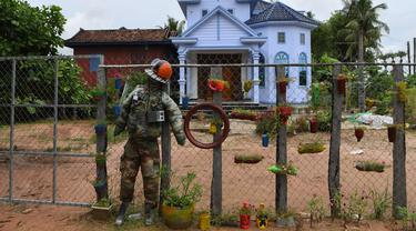 Orang-orangan sawah diikat ke pagar di depan sebuah rumah di provinsi Kampong Cham, Kamboja, 11 Oktober 2020. Para petani di desa itu menggunakan orang-orangan sawah atau disebut juga Tim Mong untuk menangkal virus corona  Covid-19 berdasarkan kepercayaan yang mereka yakini. (TANG CHHIN Sothy/AFP)