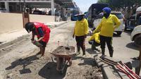 Pelanggar protokol kesehatan di Pekanbaru jalani sanksi sosial membersihkan jalan. (Liputan6.com/Pekanbaru)