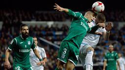 Pemain Real Madrid, Karim Benzema dan pemain Leganes, Unai Bustinza berebut menyundul bola pada leg kedua perempatfinal Copa del Rey di Santiago Bernabeu, Kamis (25/1). Bermain di kandang sendiri, Real Madrid menyerah 1-2. (AP/Francisco Seco)