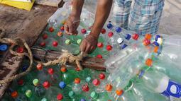Nelayan Palestina, Mouad Abu Zeid memperbaiki perahunya yang terbuat dari botol plastik bekas di pantai Rafah, Jalur Gaza, 14 Agustus 2018. Zeid menggunakan lem dan jaring bekas untuk mengikat botol menjadi perahu kecil. (AFP/SAID KHATIB)