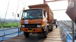 Suasana saat Menteri PUPR Basuki Hadimuljono menaiki truk untuk melintasi Jembatan Kali Kuto di Batang, Jateng, Rabu (13/6). Menurut Hadi, pengoperasian sementara jembatan ini untuk mengurai kepadatan kendaraan pemudik. (Liputan6.com/Arya Manggala)