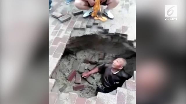 Seorang pria tua berhasil diselamatkan setelah jatuh ke lubang atau sinkhole. Menurut laporan media setempat, lubang itu terbentuk karena hujan deras.