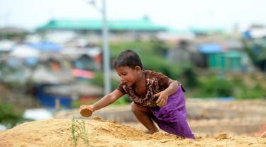 Seorang anak pengungsi Rohingya bermain pasir di Kamp Pengungsian Kutupalong, Ukhia, Bangladesh, Jumat (13/9/2019). Kamp ini adalah salah satu dari dua kamp pengungsian yang dikelola pemerintah di Cox's Bazar. (MUNIR UZ ZAMAN/AFP)