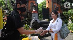 Petugas memberikan cairan hand sanitizer kepada pengurus Pura Amerta Jati menjelang persiapan Hari Raya Nyepi Saka 1942 di Cinere, Depok, Selasa (24/3/2020). Rangkaian Nyepi di sejumlah pura hanya akan dilakukan oleh panitia dalam jumlah terbatas untuk mencegah Covid-19. (merdeka.com/Arie Basuki)