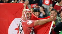 Ekspresi pendukung Timnas Tunisia saat menyaksikan pertandingan antara Tunisia melawan Libya di kualifikasi Piala Dunia 2018 di Stadion Olimpiade Rades, Tunisia (11/11). Tunisia berhasil lolos ke Piala Dunia 2018. (AFP Photo/Fethi Belaid)