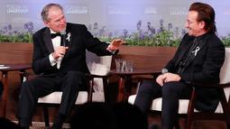 Presiden AS ke-43 George W. Bush berdiskusi dengan vokalis U2 Bono selama gala untuk Forum Kepemimpinan di Institut George W. Bush di Dallas, AS (19/4). Dalam acara ini Bush mempersembahkan Bono medali Distinguished Citizenship. (AP Photo/Brandon Wade)