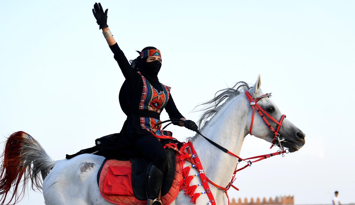 Perempuan Arab melambaikan tangan saat menunggangi kuda dalam Festival Souk Okaz 2019 di Kota Taif, Arab Saudi, Rabu (7/8/2019). Tahun ini merupakan pertama kalinya perempuan diizinkan untuk berpartisipasi dalam Festival Souq Okaz 2019. (AMER HILABI/AFP)