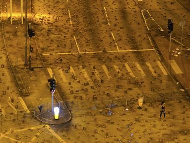 Seorang wanita berjalan di persimpangan lampu lalu lintas yang berserakan dengan batu bata yang dipasang oleh pengunjuk rasa pro-demokrasi di luar kampus Universitas Baptis Hong Kong (13/11/2019). Mahasiswa dari China daratan dan Taiwan meninggalkan Hong Kong. (AP Photo/Vincent Yu)