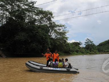 Sejumlah siswa menyeberangi sungai Ciberang mengunakan perahu karet milik BNPB di Lebak, Banten, Senin (16/3). Pasca robohnya jembatan gantung di atas Sungai Ciberang, warga terpaksa menyeberang mengunakan perahu karet. (Liputan6.com/Herman Zakharia)
