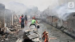Warga bergotong royong mengambil air dari kali saat berusaha menjinakkan kebakaran di Jalan Kebon Jeruk 13, Taman Sari, Jakarta Barat, Minggu (6/10/2019). Kebakaran diduga akibat anak bermain korek api. (merdeka.com/Iqbal Nugroho)