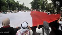 Massa GJI membentangkan bendera Merah Putih raksasa saat menggelar aksi menuntut Gubernur DKI Jakarta Anies Baswedan untuk mencabut izin penyelanggaraan Reuni 212 di depan Balai Kota, Jakarta, Kamis (29/11). (Merdeka.com/Iqbal S. Nugroho)