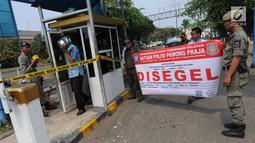 Petugas Satuan Polisi Pamong Praja (Satpol PP) Kota Tangerang Selatan memasang spanduk penyegelan areal parkir liar di kawasan BSD, Rabu (3/10). Penyegelan tersebut dilakukan lantaran pihak pengelola parkir tidak memiliki izin. (Merdeka.com/Arie Basuki)