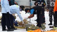 Tim Komite Nasional Keselamatan Transportasi (KNKT) memeriksa serpihan pesawat Sriwijaya Air SJ 182 yang berhasil dtemukan dan dievakuasi tim SAR gabungan di Dermaga JICT, Jakarta, Minggu (10/1/2021). Sriwijaya Air SJ 182 jatuh di perairan Kepulauan Seribu. (Liputan6.com/Helmi Fithriansyah)