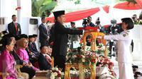 Presiden Jokowi (kiri) menyerahkan bendera Merah Putih kepada anggota Paskibraka Maria Felicia Gunawan saat Upacara Peringatan Detik-detik Proklamasi 17 Agustus di halaman Istana Merdeka, Jakarta, Senin (17/8/2015). (Liputan6.com/Faizal Fanani)