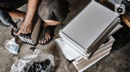 Aktivitas pekerja saat menyelesaikan produksi papan tulis di Jakarta, Rabu (3/3/2021). Selama pandemi, rata-rata dalam sehari sebanyak 15 buah papan tulis laris terjual berkat pemasaran online di masa pandemi covid-19. (merdeka.com/Iqbal S Nugroho)