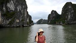 Wisatawan domestik berpose untuk foto di atas kapal di tengah Ha Long Bay, Quang Ninh, Vietnam, (16/5/2020). Seiring dengan meredanya virus corona, Ha Long Bay kawasan yang menjadi situs warisan dunia UNESCO kembali didatangi ratusan wisatawan. (AFP/Manan Vatsyayana)