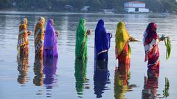 Sejumlah perempuan Hindu India membawa sesajen ketika berdoa pada matahari di tepi Danau Hussain Sagar di Hyderabad saat Festival Chhath untuk memuja dewa matahari, Selasa (17/11). (AFP PHOTO/NOAH Seelam)