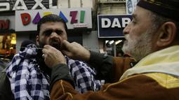 Seorang pria di Lebanon ditusuk pipinya dengan jarum panjang saat memperingati kelahiran Nabi Muhammad, Lebanon, Sabtu (3/1/2015). (AFP Photo/Mahmud Zayyat)