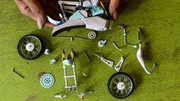 Seorang pekerja memasang bagian-bagian dari miniatur sepeda motor di bengkel kerjanya di Kelurahan Serua, Tangerang Selatan, Banten (10/10/2020). Di sana, miniatur sepeda motor yang terbuat dari bahan-bahan daur ulang dijual kepada pelanggan sebagai hadiah atau hiasan. (Xinhua/Agung Kuncahya B.)