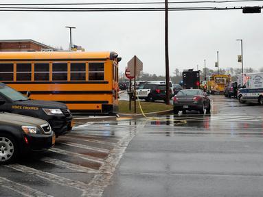 Sejumlah kendaraan dari petugas keamanan dan bus sekolah terparkir di dekat pintu masuk Great Mills High School di Maryland, AS (20/3). Seorang pelaku penembakan bernama Austin Wyatt Rollins melukai dua siswa di sekolah tersebut. (AP Photo / Alex Brandon)