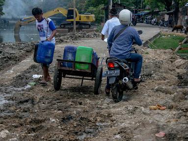 Penjual air bersih mengantarkan air ke Rusun Sidang, Jakarta, Senin (22/9/14). (Liputan6.com/Faizal Fanani)