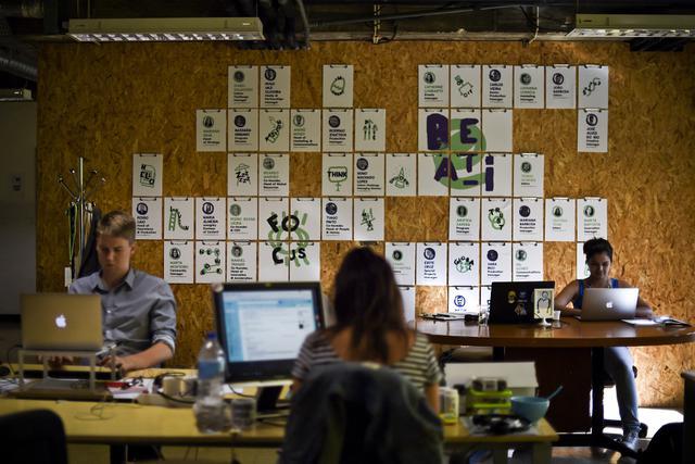 Pengusaha muda bekerja di depan komputer di pusat startup teknologi