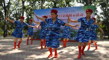 Para wanita lansia melakukan tarian dengan mengenakan pakaian bergaya militer saat mengikuti Hari Kebugaran Nasional di Beijing, Tiongkok (8/8). Hari tersebut juga bertepetan dengan hari pembukaan Olimpiade Beijing 2008. (AFP Photo/Greg Baker)