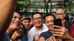 Gubernur Jawa Barat Ridwan Kamil berswafoto bersama warga saat Family Day Artha Graha Peduli (AGP) di Pasar Akhir Pekan SCBD, Jakarta, Minggu (25/11). Emil menyambut positif kegiatan ini sebagai langkah untuk menjaga kesehatan. (Liputan6.com/Fery Pradolo)