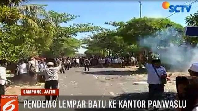 Polisi terpaksa menembakkan gas air mata, saat massa pendemo bertindak anarkis, dengan melempar batu ke arah Kantor Panwaslu.