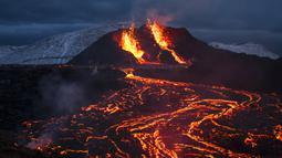 Pemandangan aliran lahar dari letusan gunung berapi di Semenanjung Reykjanes, barat daya Islandia, Senin (29/3/2021). Letusan gunung berapi tersebut masih menarik ribuan orang yang berharap untuk mendekati aliran lahar. (AP Photo/Marco Di Marco)