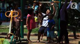 Anak-anak bermain di Taman Kota Waduk Pluit di Penjaringan, Jakarta Utara, Minggu (27/12/2020). Taman Kota Waduk Pluit dibuka kembali setelah di tutup pada libur Natal, namun banyak warga yang berwisata tidak menerapkan protokol kesehatan. (Liputan6.com/Johan Tallo)