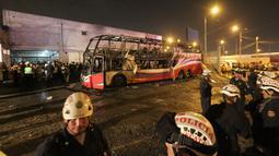 Petugas kepolisian berdiri dekat kerangka  bus bertingkat yang hangus terbakar di terminal bus antarprovinsi, kota Lima, Peru, Minggu (31/3). Pihak berwenang masih menyelidiki penyebab pasti mengapa bus yang penuh penumpang itu ludes dilalap api. (Photo by Luka GONZALES / AFP)