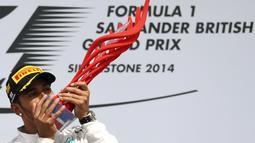 Selebrasi pembalap Formula Satu dari tim Mercedes, Lewis Hamilton, usai memenangi GP Inggris yang dihelat di Sirkuit Silverstone, (6/7/2014). (REUTERS/Francois Lenoir)