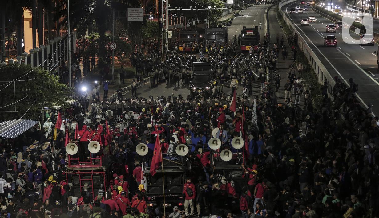 Mahasiswa dan elemen buruh bertahan hingga malam saat aksi di depan Gedung DPR/MPR/DPD, Jakarta, Kamis (16/7/2020). Dalam aksinya, mereka menolak pengesahan RUU Cipta Kerja atau Omnibus Law yang saat ini sedang dibahas DPR bersama pemerintah. (Liputan6.com/Johan Tallo)
