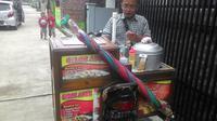 Nampak pedagang cilok keliling tengah melayani pembeli (Liputan6.com/Jayadi Supriadin)