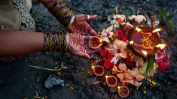 Umat Hindu India melakukan ritual selama Festival Chhath Puja di tepi sungai Brahmaputra, Gauhati, Selasa (13/11). Festival Hindu kuno ini dilakukan sebagai bentuk terima kasih kepada Dewa Matahari yang menopang kehidupan di bumi. (AP/Anupam Nath)